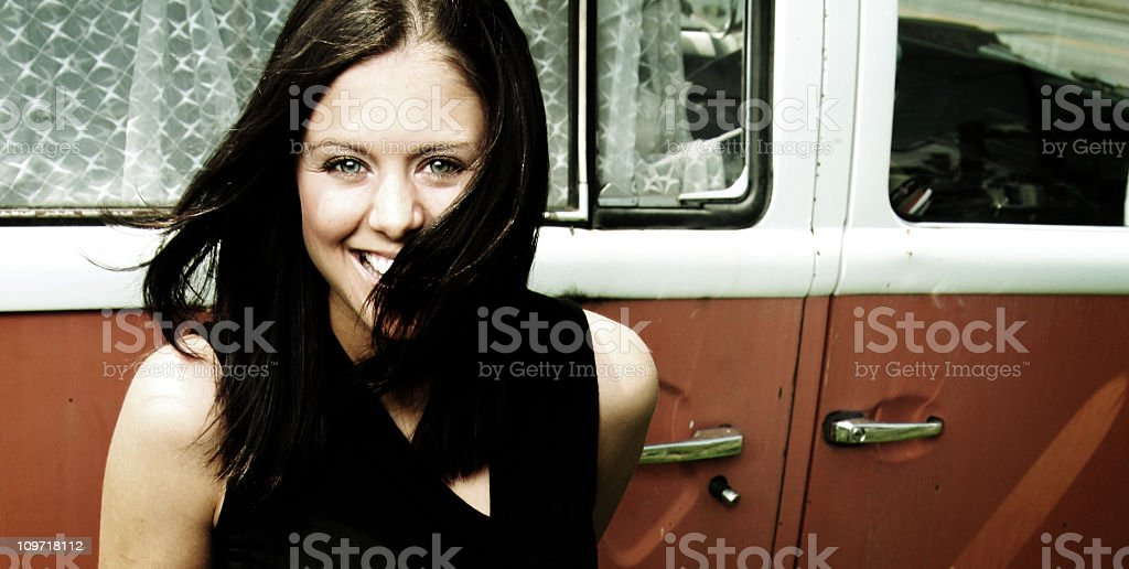 Portrait of Young Woman Smiling Against Old Bus royalty-free stock photo