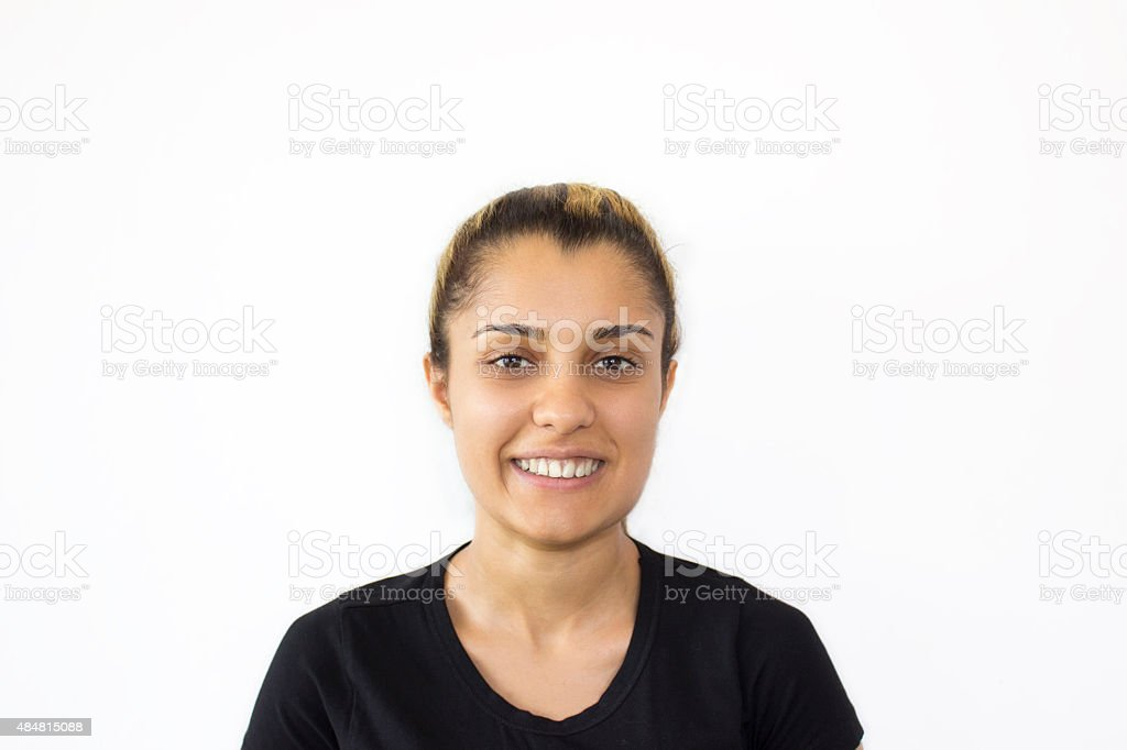Portrait of young woman smiling against white background stock photo