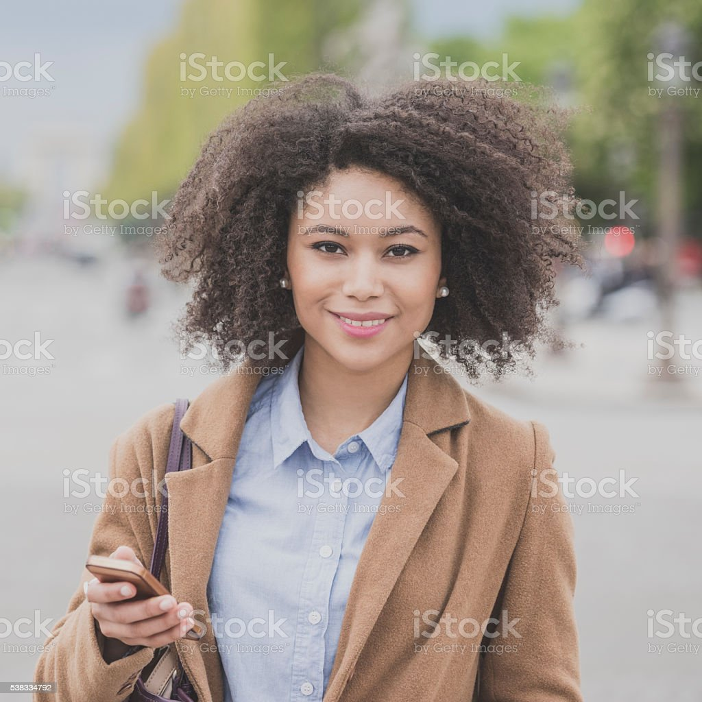 Portrait of young woman smiling towards camera with phone stock photo