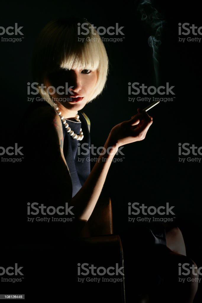Portrait of Young Woman Smoking Cigarette, Low Key royalty-free stock photo