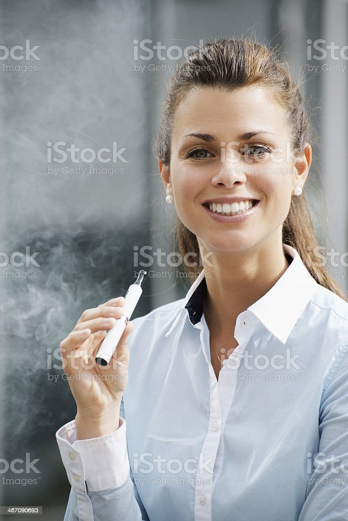 portrait of young woman smoking electronic cigarette outdoor royalty-free stock photo