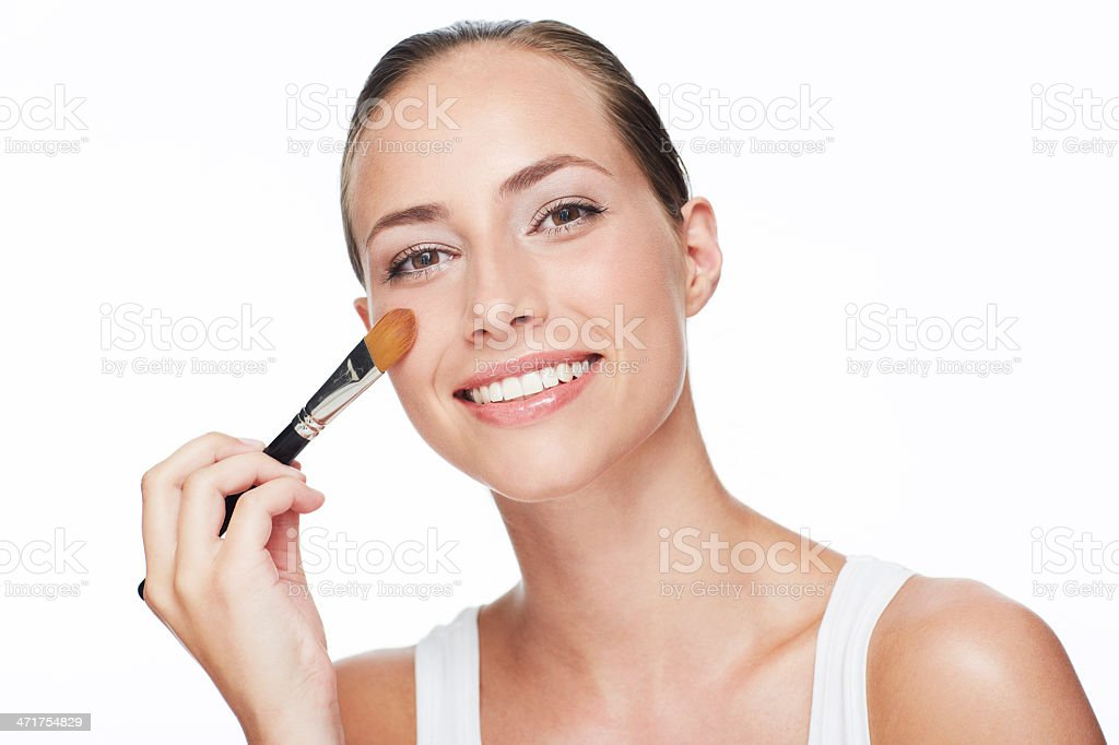 Portrait of young woman using blusher brush stock photo