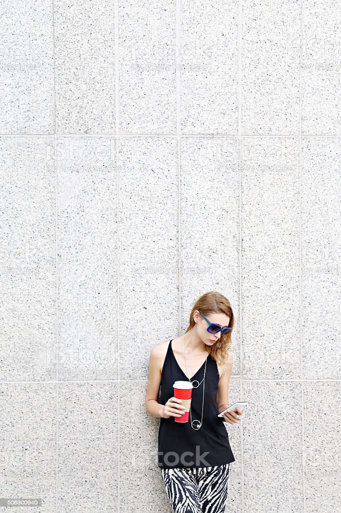 Portrait of young woman with coffee and cell phone stock photo