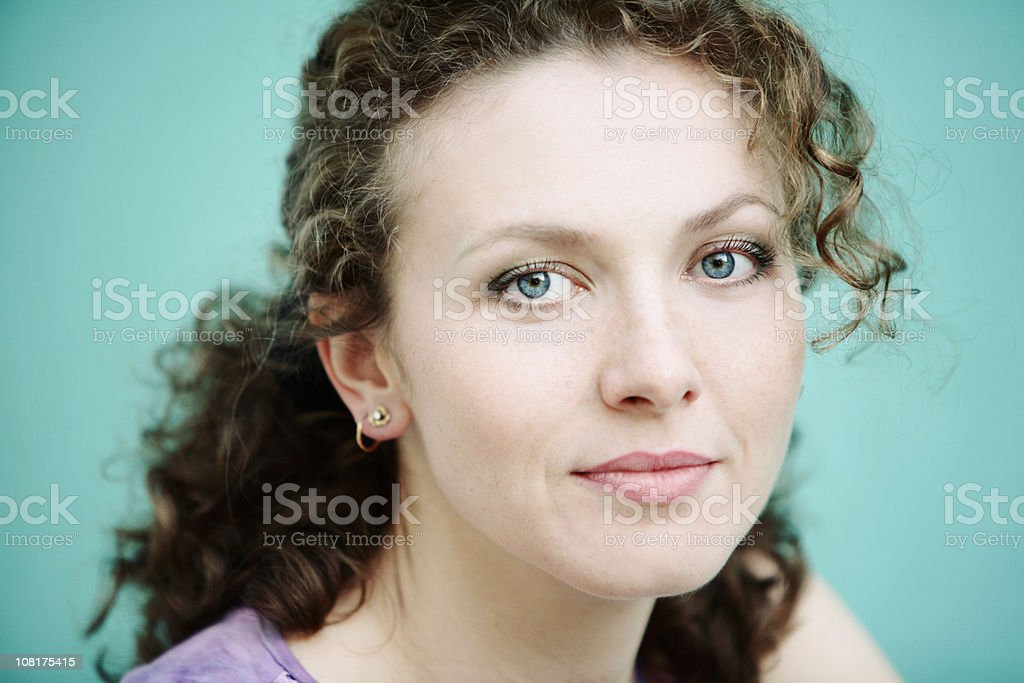 Portrait of Young Woman With Curly Hair on Blue Background royalty-free stock photo