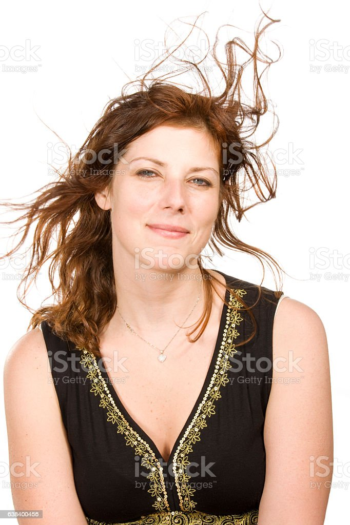 Portrait of young woman with hair blowing on white background stock photo