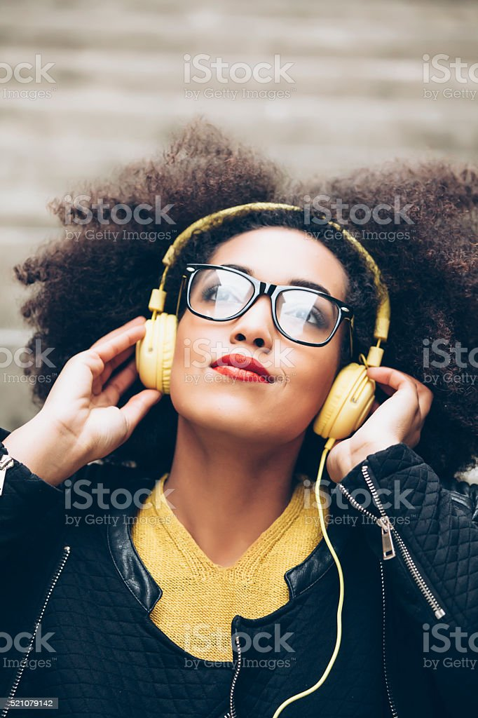 Portrait of young woman with yellow headphones-close up stock photo