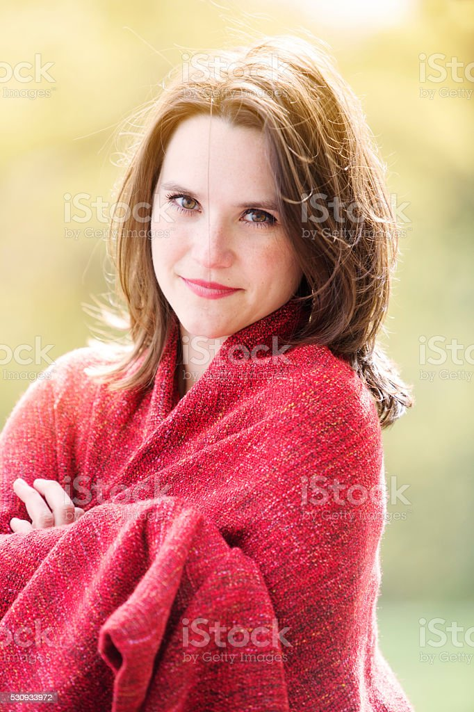portrait of young woman wrapped in blanket outdoors stock photo