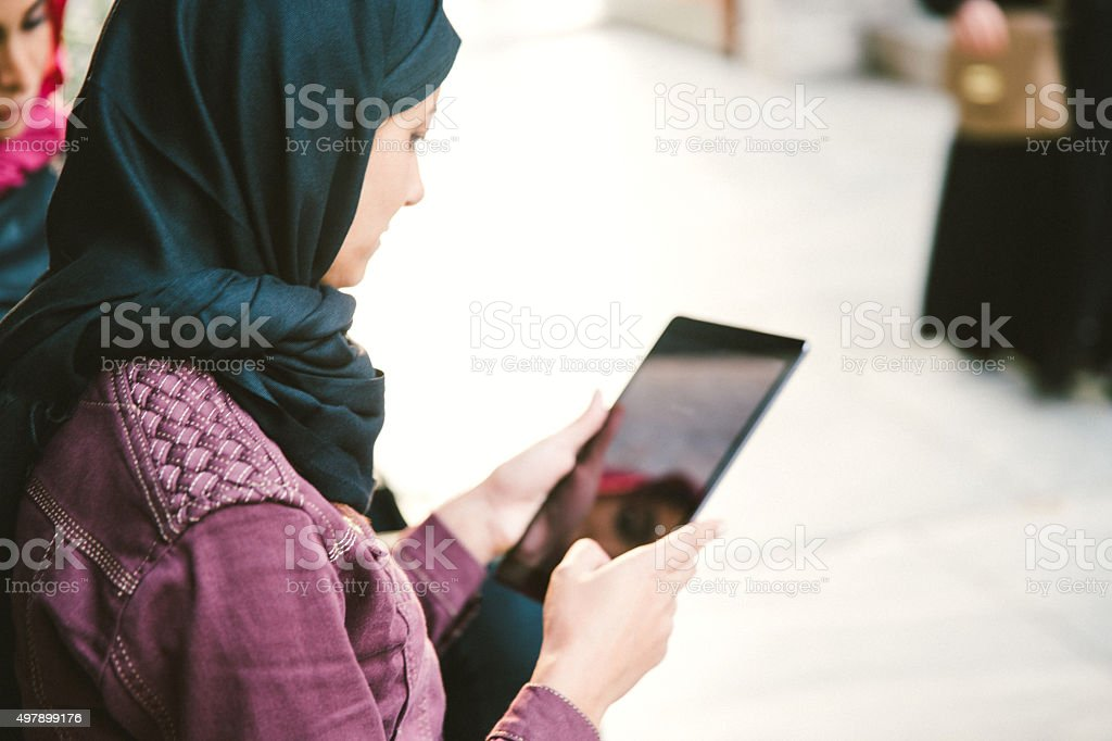 Portrait Of Young Women Wearing Headscarf Reading Books Outdoors stock photo