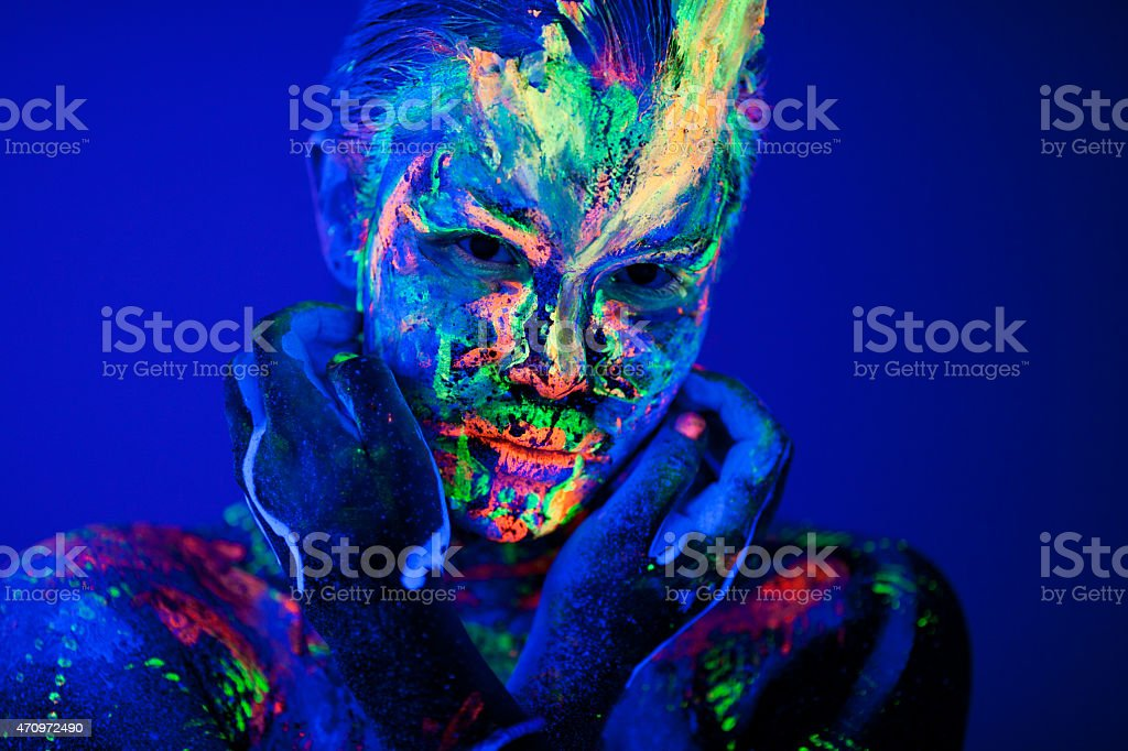 Portrait painted with fluorescent makeup under the ultraviolet light stock photo