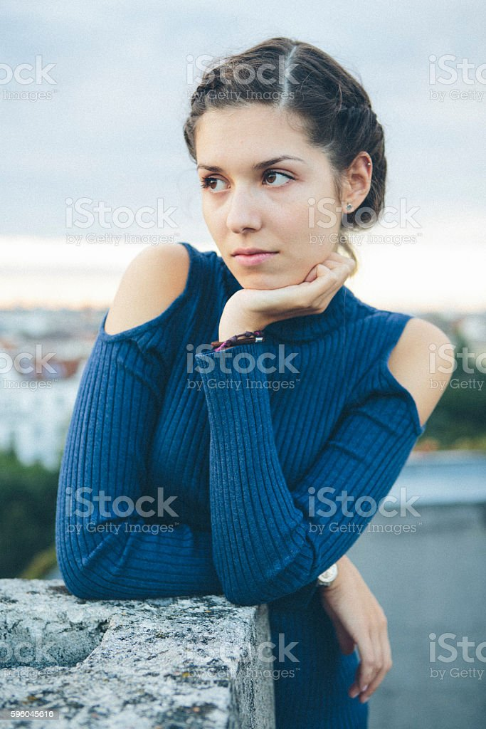 portrait: pensive young woman with with hair bun, looking away stock photo