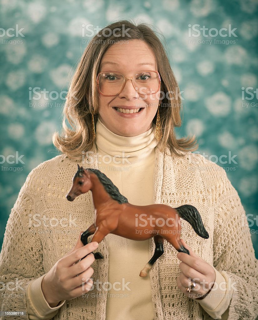 Portrait Photograph of Blond Woman Holding Toy Horses 3 royalty-free stock photo