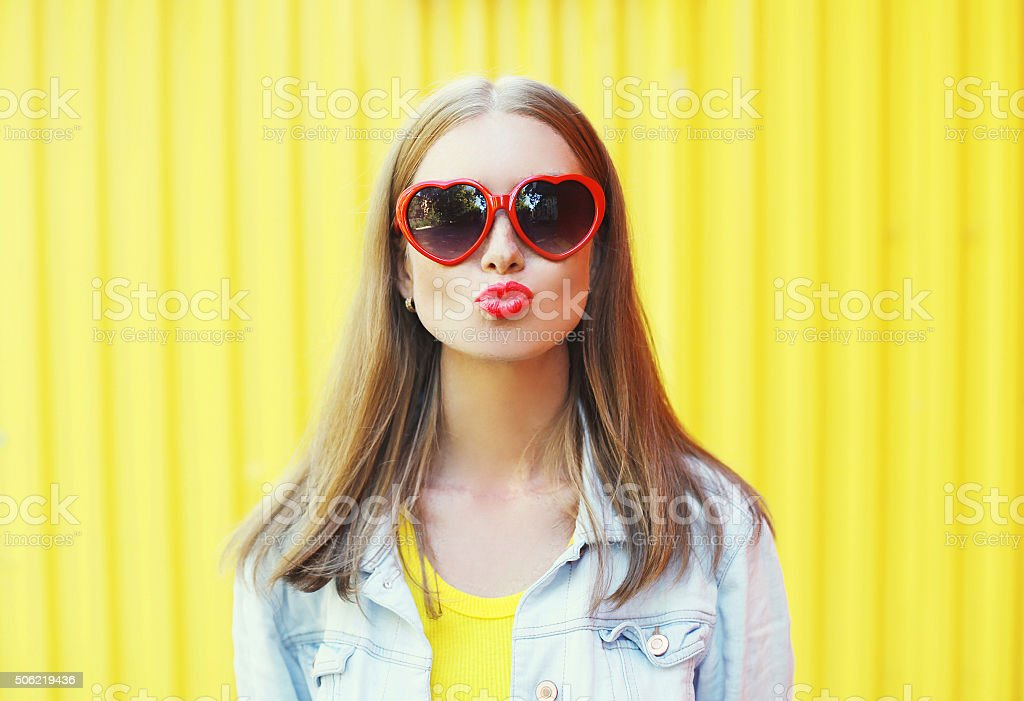 Portrait pretty young woman in red sunglasses blowing lips kiss stock photo