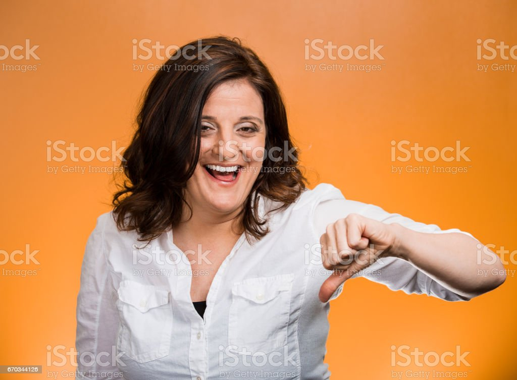 Portrait sarcastic woman showing thumbs down hand gesture happy someone made mistake lost stock photo