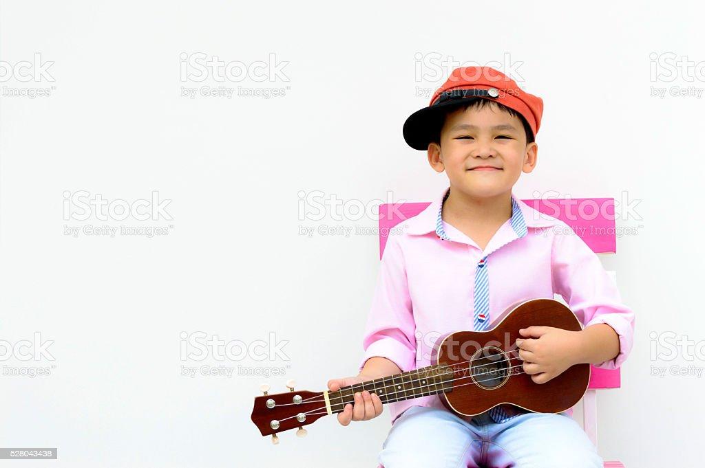 Portrait smart Asian kid play ukulele stock photo