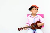 Portrait smart Asian kid play ukulele