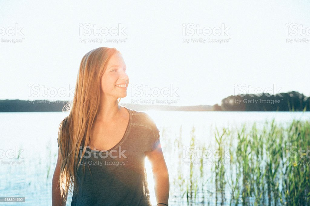 portrait smiling young blonde woman on nature background stock photo