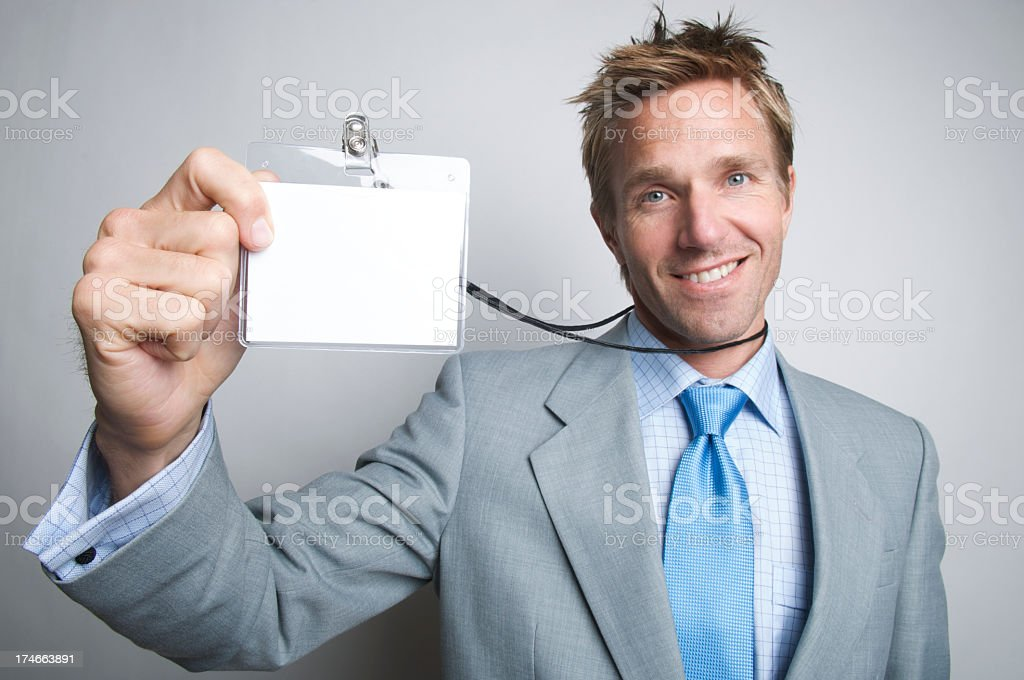 Portrait smiling young businessman holding up ID stock photo