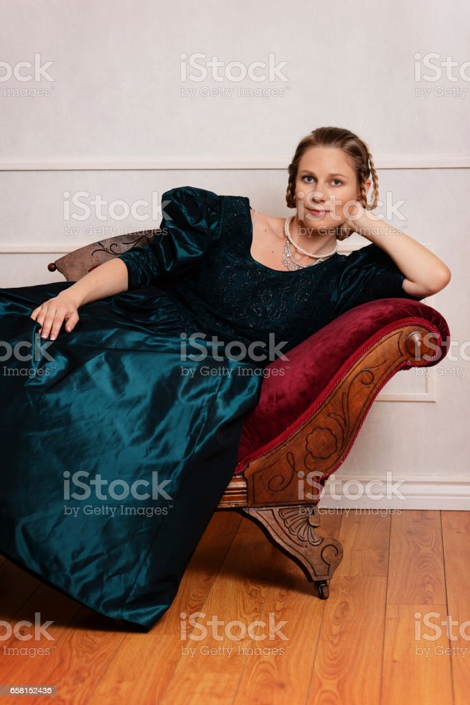 portrait victorian woman leaning on fainting couch stock photo