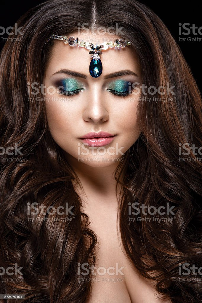 Portrait with green jewelry closeup isolated on black background. stock photo