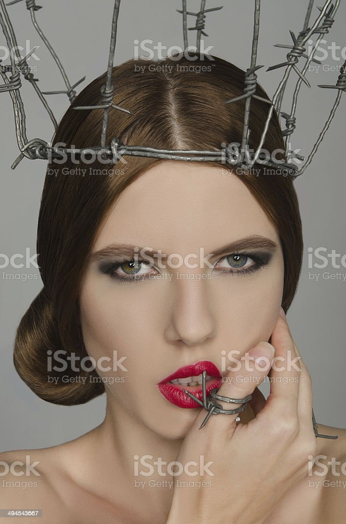 Portrait woman in crown and ring of barbed wire stock photo