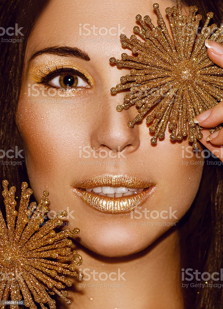 Portrait woman with Christmas decorations snowflakes. Fashion gold make-up. stock photo