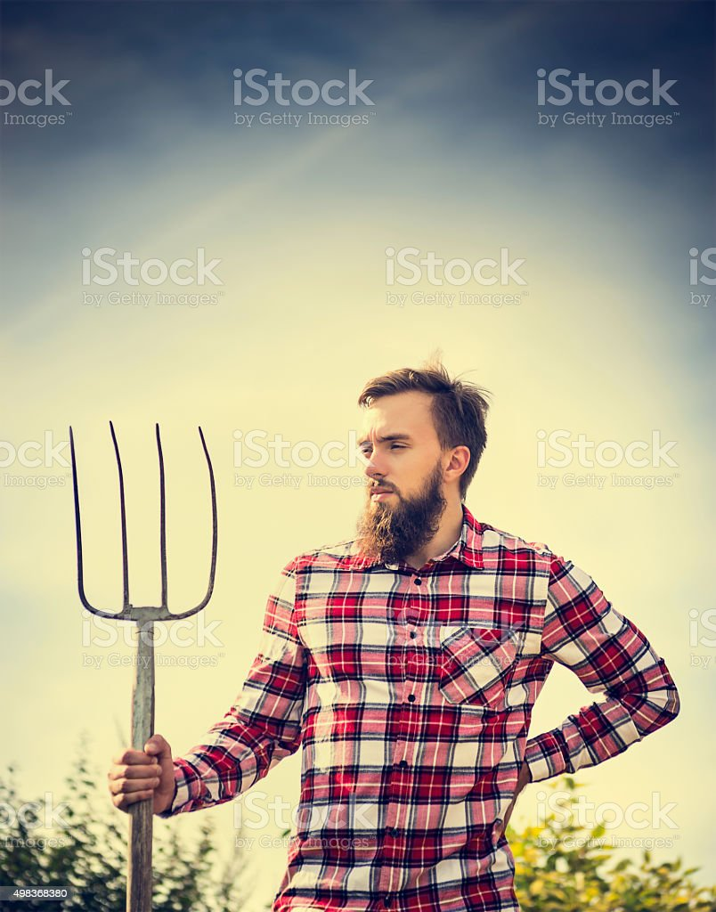 Portrait young bearded farmer  checkered shirt old pitchfork stock photo