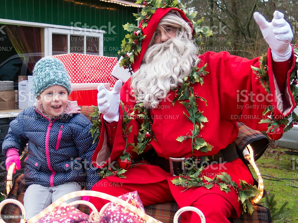 Portret of child with Father Christmas on sleigh, Netherlands stock photo