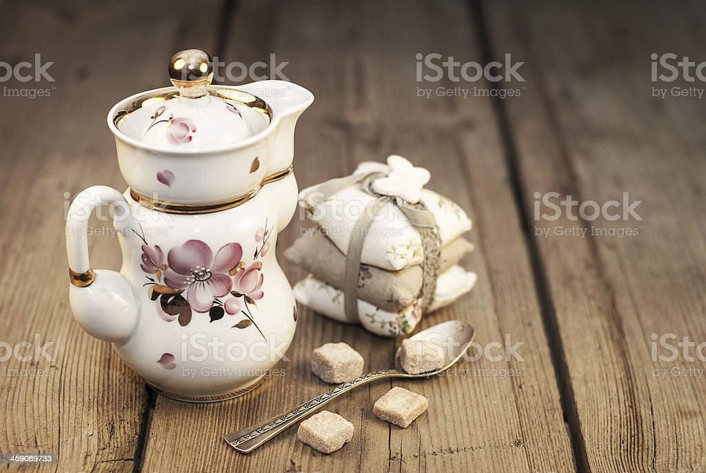 Portselana tea pot and silver spoon with sugar stock photo