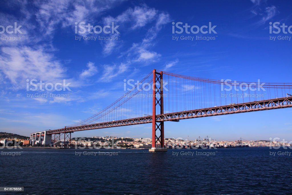 Portugal, The 25th April Bridge and historical Lisbon viewed from the Tagus River estuary. stock photo