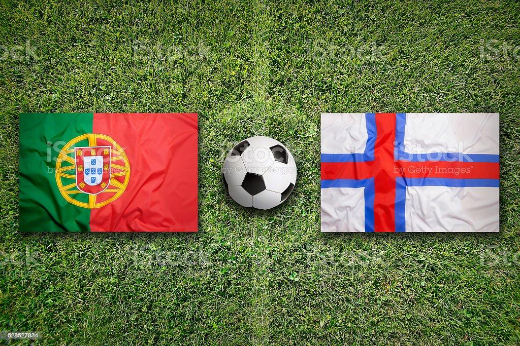 Portugal vs. Faeroe Islands flags on soccer field stock photo