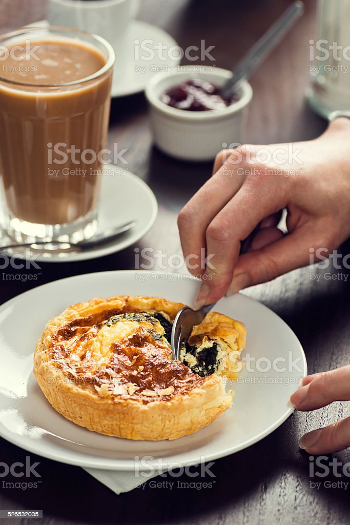 Portuguese Breakfast Cutting Into Spinach and Cheese Quiche with Coffee stock photo