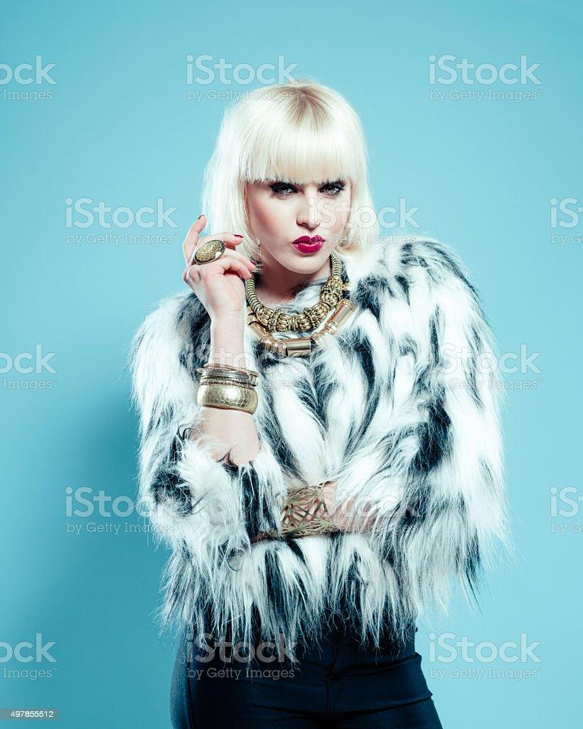Posh blonde woman wearing fur jacket and gold jewlery stock photo