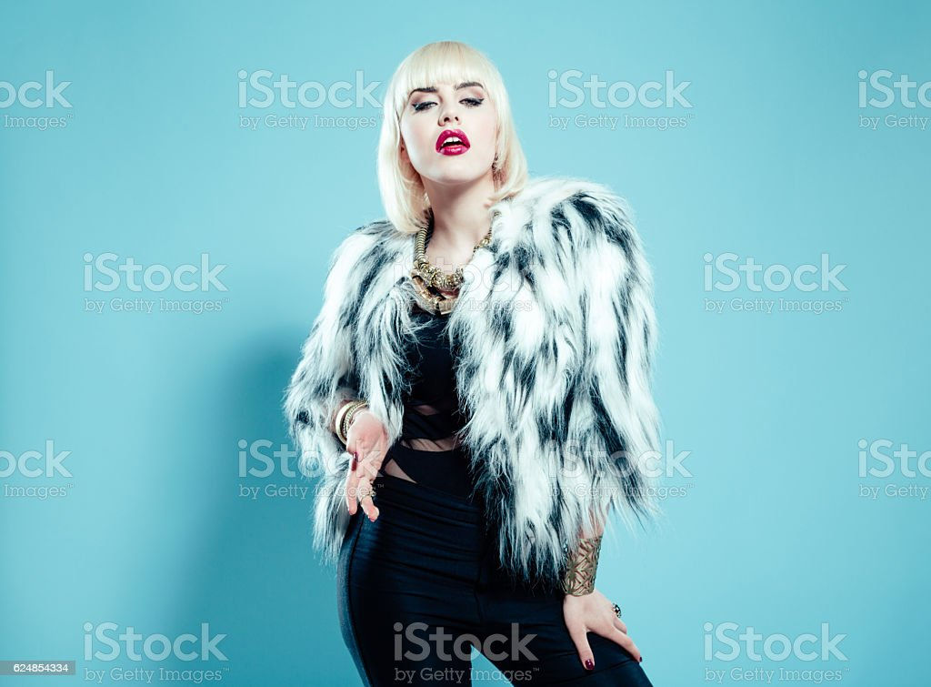 Posh blonde woman wearing fur jacket and gold jewlery stock photo