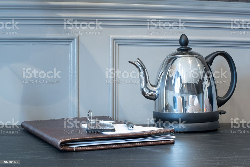 Posh hotel room with guest book and kettle stock photo
