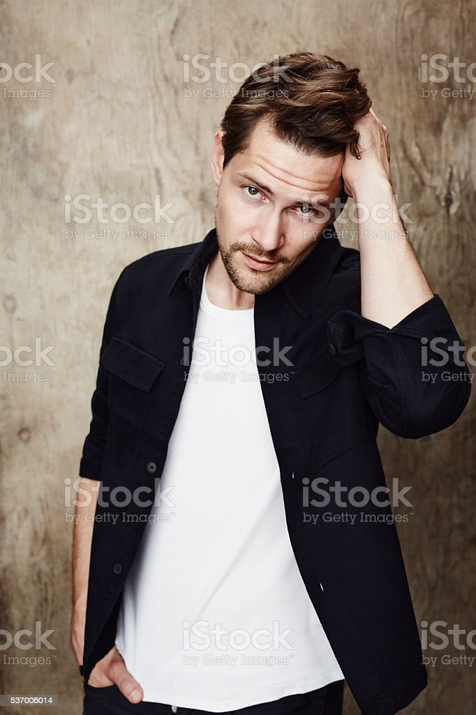 Posing dude in black shirt, looking at camera stock photo