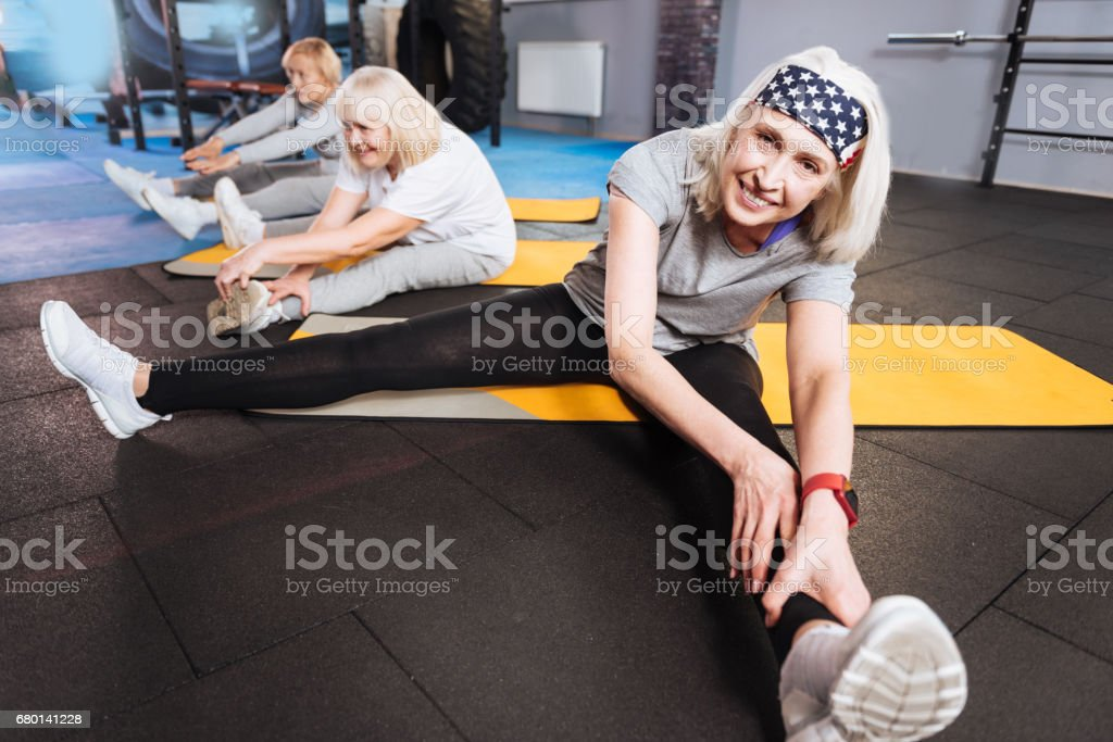 Active lifestyle. Positive happy active woman sitting on the yoga mat...