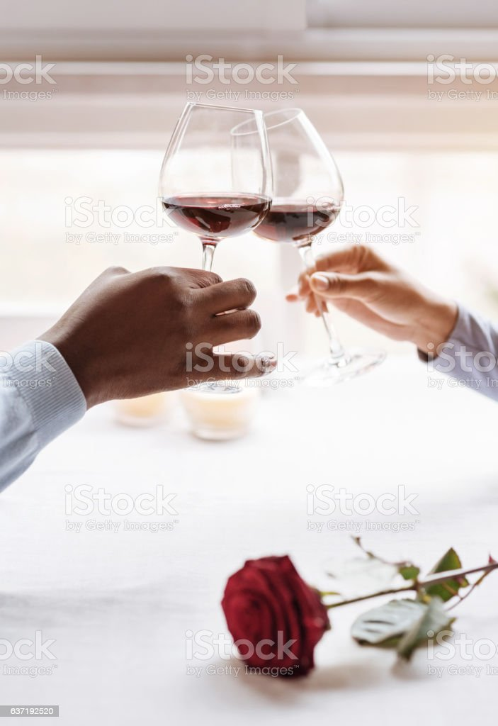 Positive African American couple drinking wine in the restaurant stock photo