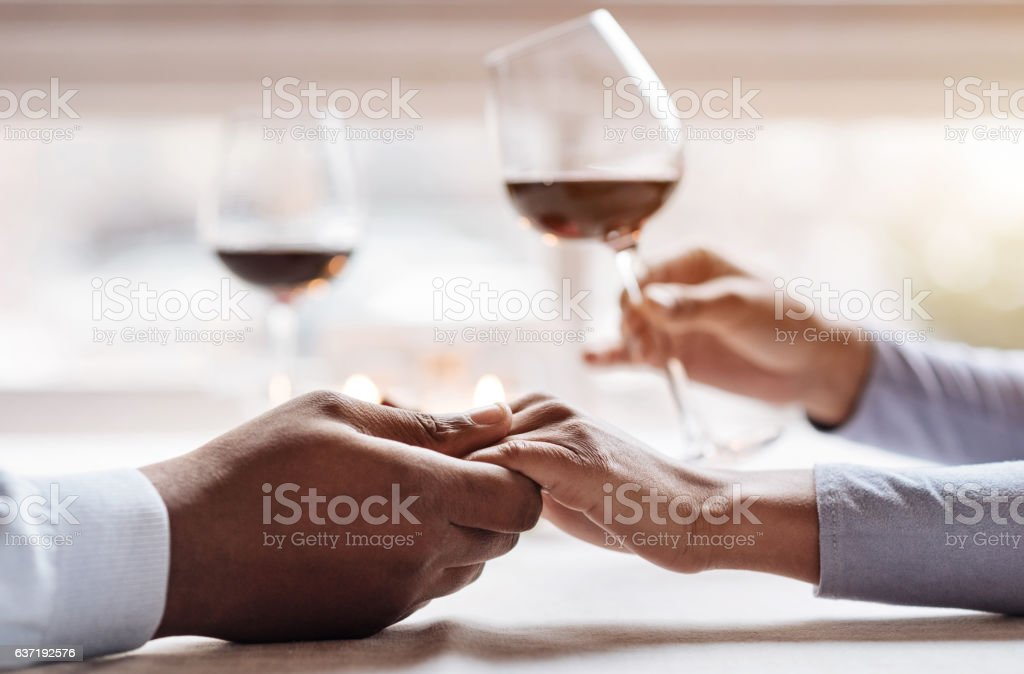 Positive African American couple enjoying the beverage in the restaurant stock photo