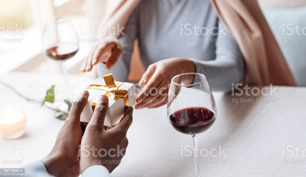 Positive African American man giving the present to his girlfriend stock photo