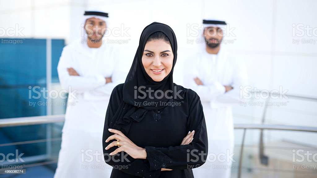 Positive Arab Female Enterpreneur With Two Men In Background stock photo