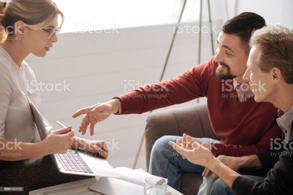 Positive bearded man pointing at the laptop screen stock photo