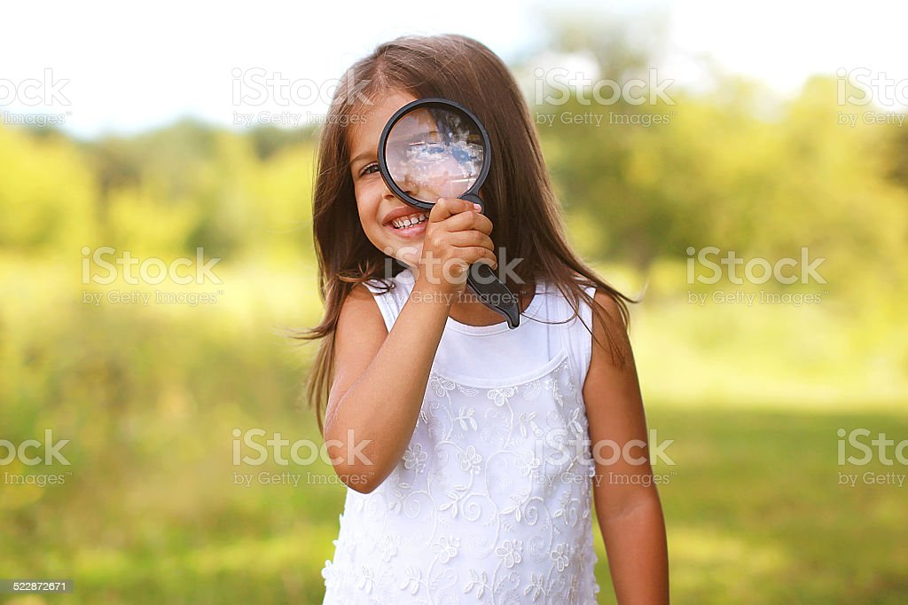 Positive cheerful little girl looking through a magnifying glass stock photo