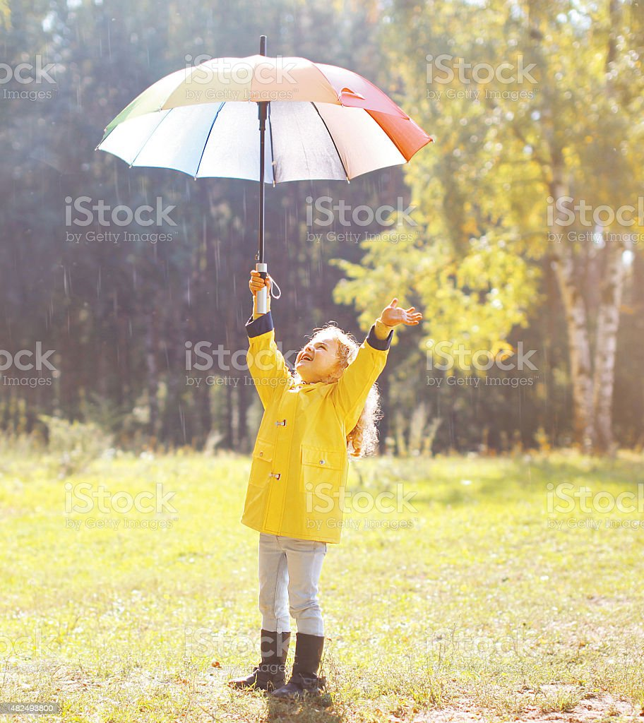 Positive child with colorful umbrella having fun in autumn day stock photo
