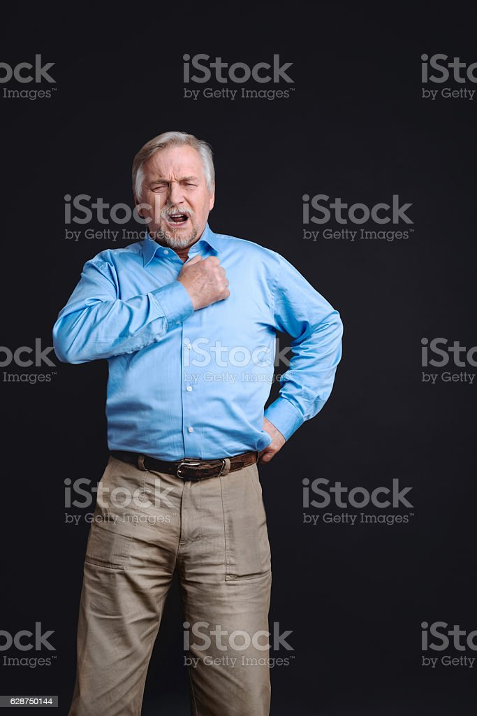 Positive confident man holding hand on the belt stock photo