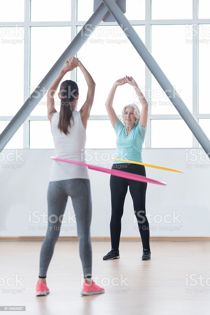 Positive confident women using hula hoops for training stock photo