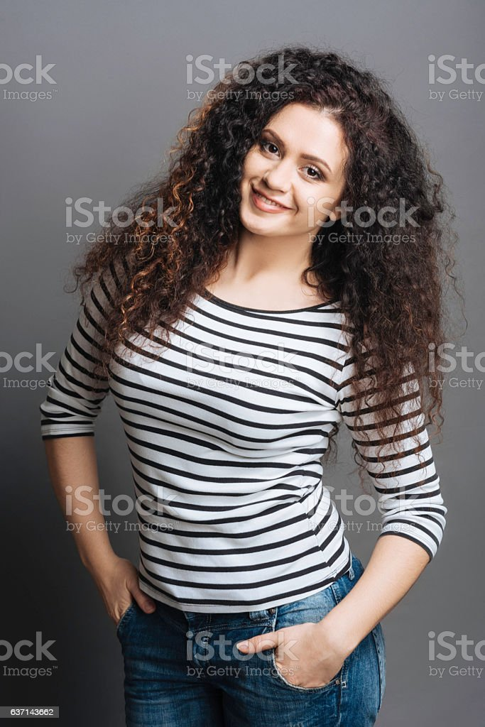 Positive delighted brunette holding hands in pockets stock photo