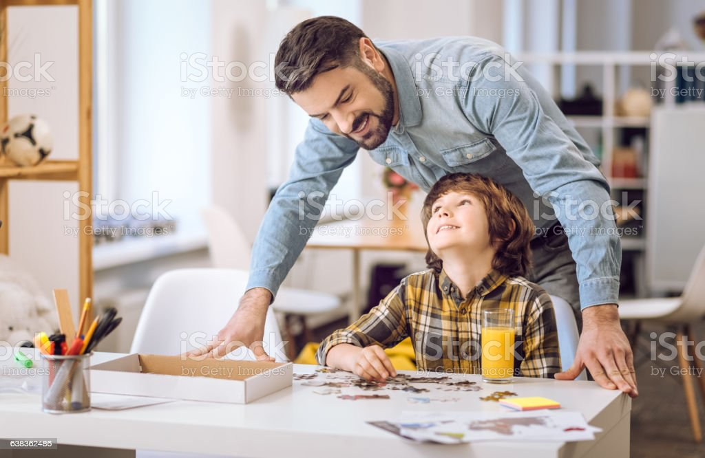 Positive delighted male standing behind son stock photo