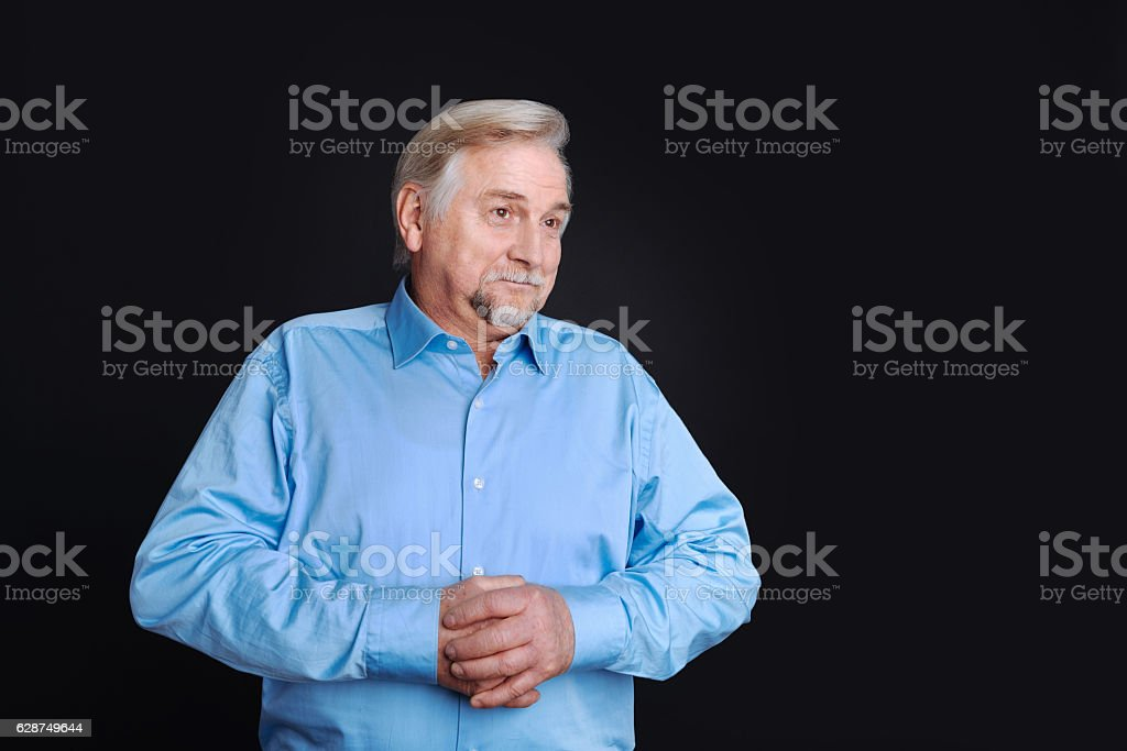 Positive delighted pensioner looking aside stock photo