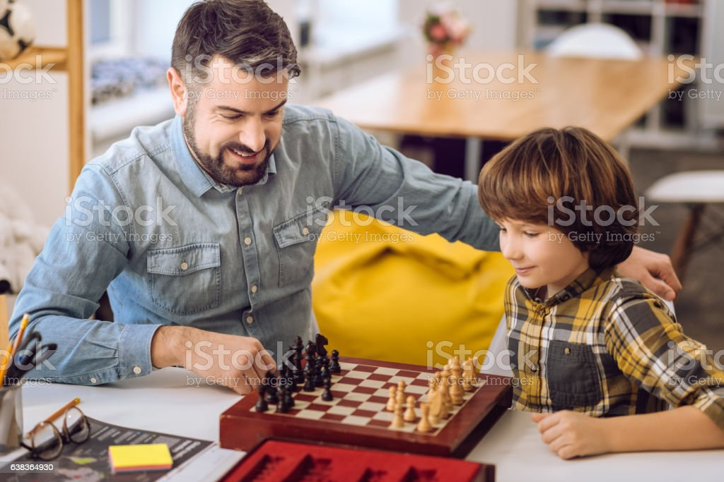 Positive delighted relatives playing chess stock photo