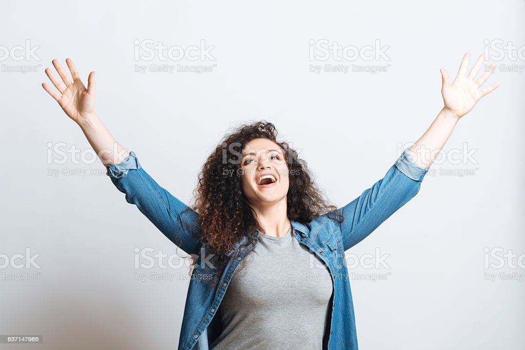 Positive delighted woman raising hands stock photo
